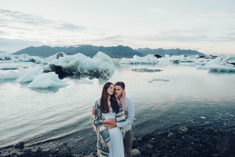 Coppie sorridenti alla moda felici che camminano e che baciano in Islanda, sopra fotografia stock