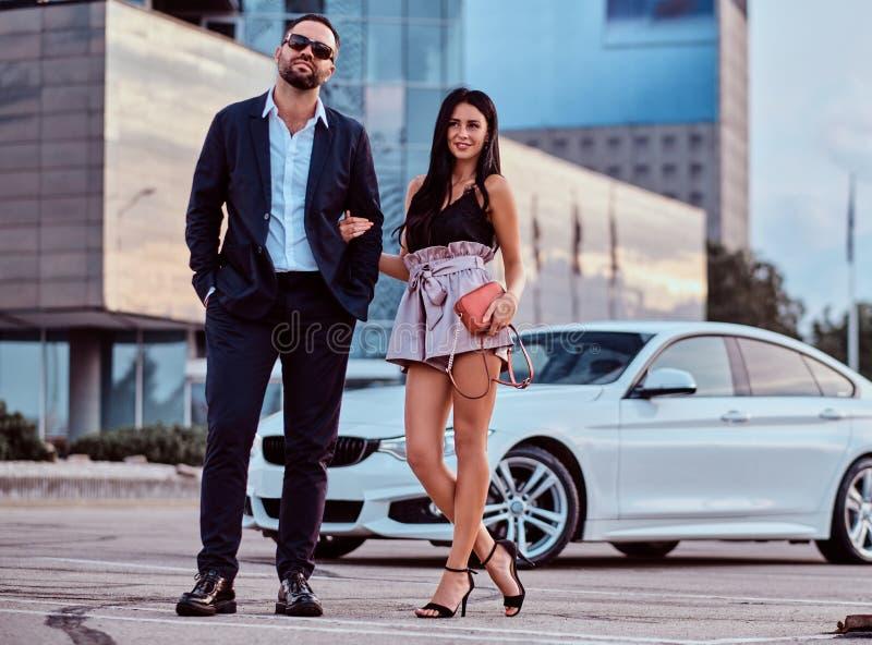 Coppie sorridenti ben vestito che posano insieme vicino all'automobile di lusso contro un grattacielo fotografia stock libera da diritti