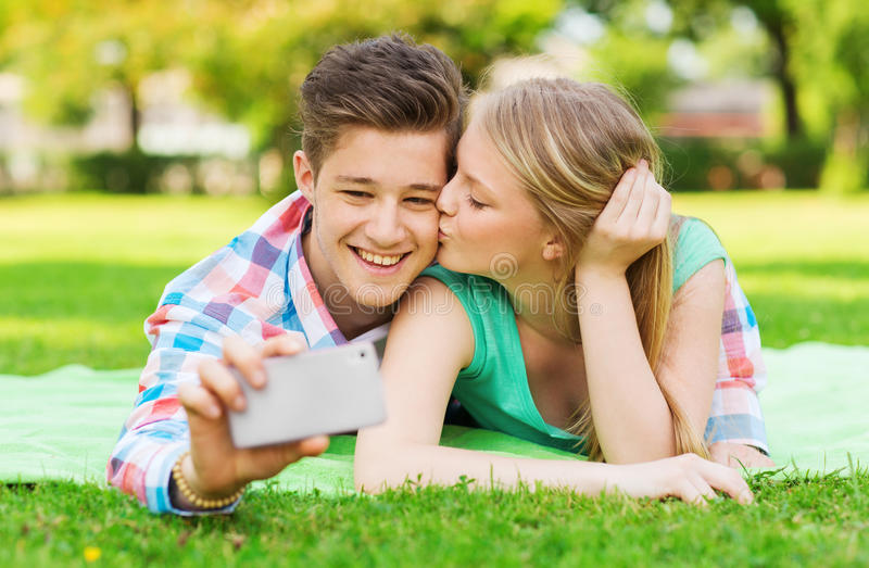 Coppie sorridenti che fanno selfie e che baciano nel parco immagini stock