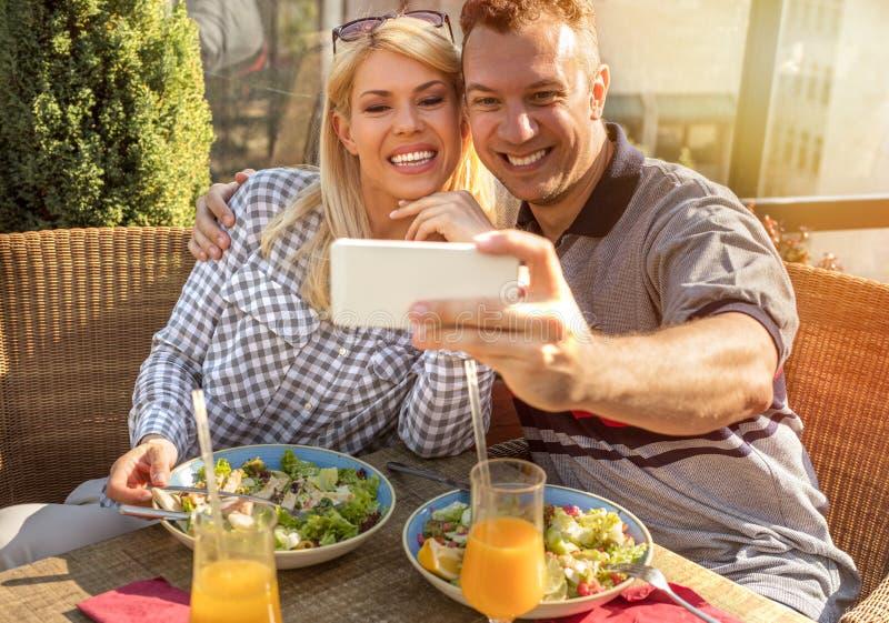 Coppie sorridenti che prendono selfie nel ristorante fotografia stock libera da diritti