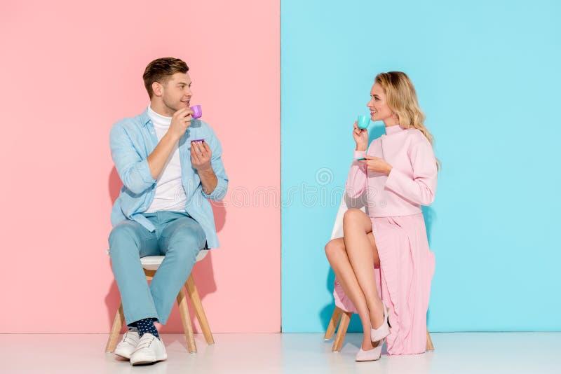 coppie sorridenti che si siedono sulle sedie, esaminantese e beventi caffè immagini stock