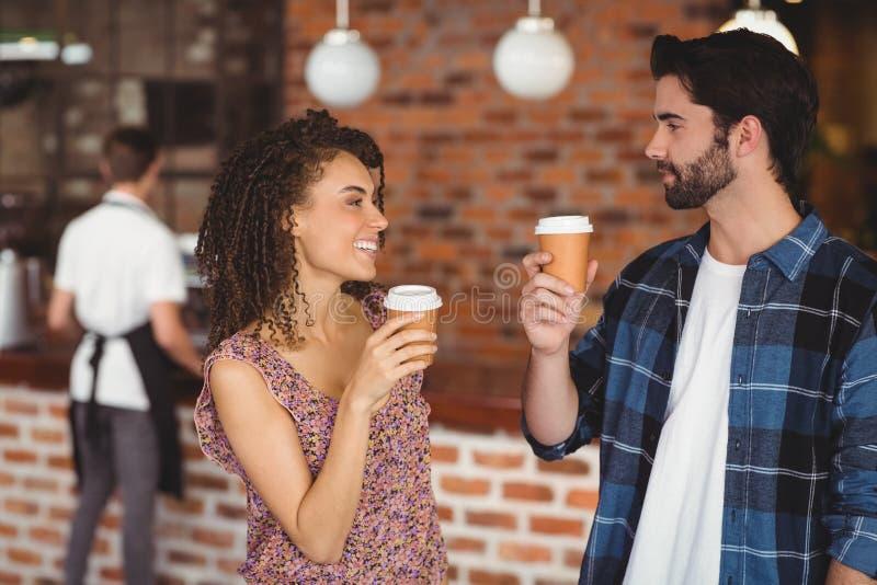 Coppie sorridenti dei pantaloni a vita bassa con le tazze asportabili fotografia stock