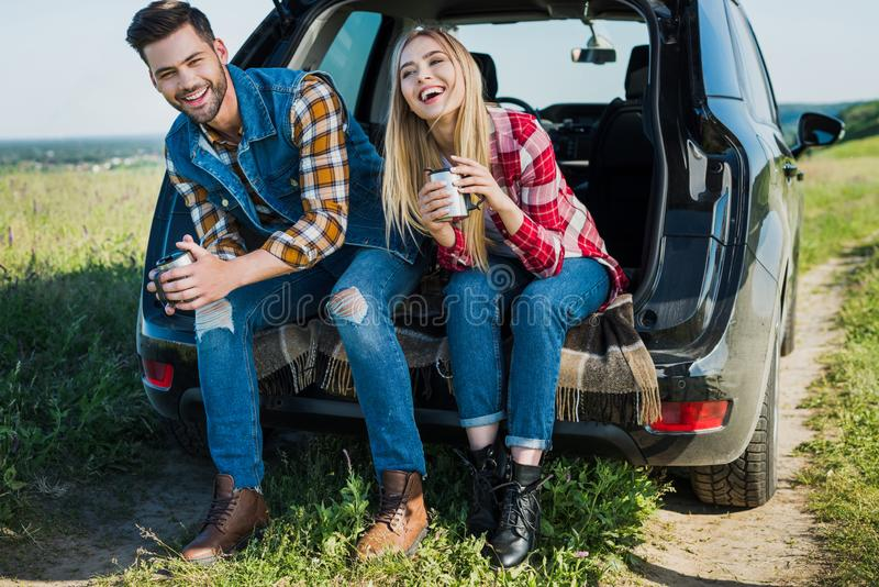 coppie sorridenti dei turisti alla moda con le tazze di caffè che si siedono sul tronco di automobile in rurale fotografia stock libera da diritti