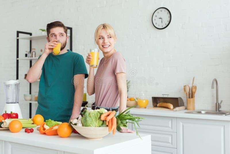 coppie sorridenti dei vegani che bevono succo fresco alla cucina immagine stock