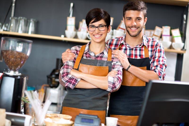 Coppie sorridenti della caffetteria del proprietario immagini stock