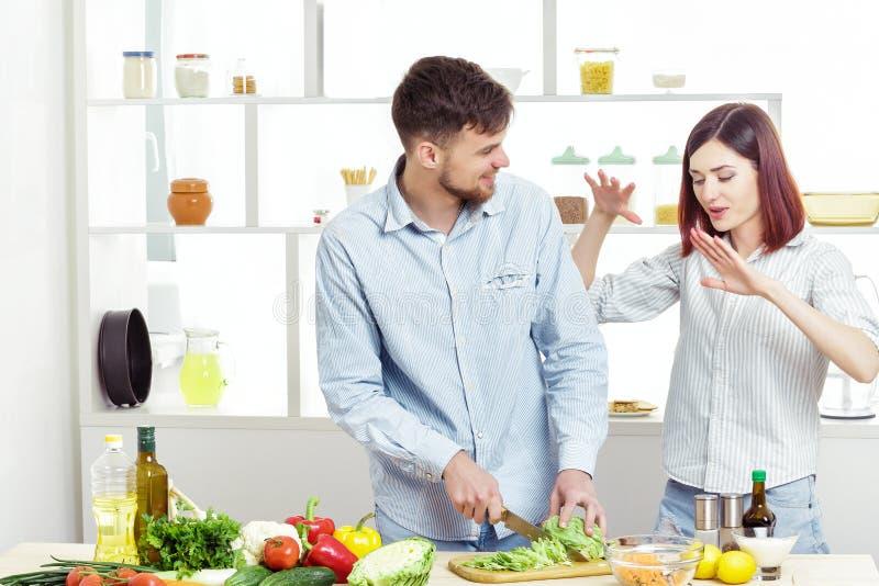 Coppie sorridenti di amore che preparano insalata sana degli ortaggi freschi in cucina fotografie stock
