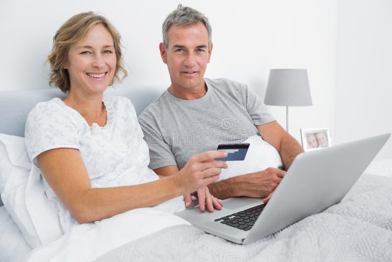Coppie sorridenti facendo uso del loro computer portatile da comprare online immagine stock libera da diritti