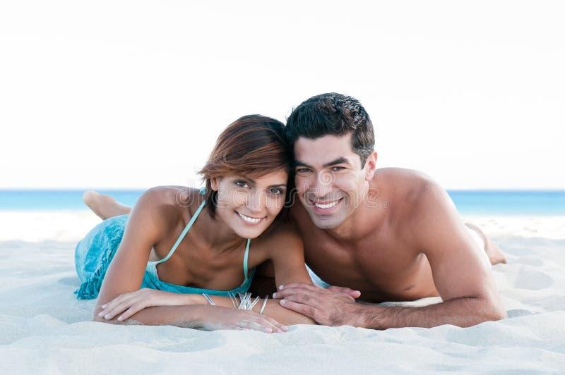 Coppie sorridenti felici alla spiaggia fotografia stock