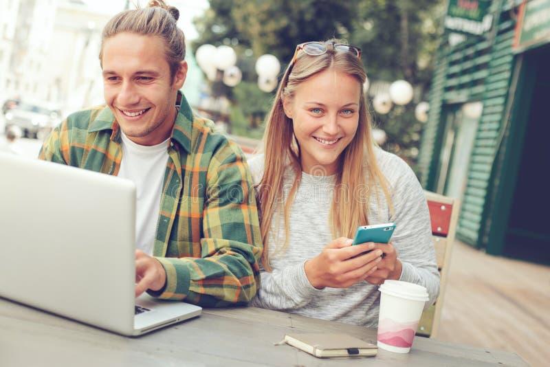 Coppie sorridenti felici in caffè della via, facendo uso del telefono e del computer portatile fotografie stock