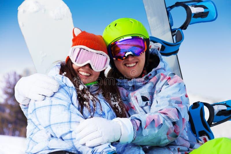 Coppie sorridenti nell'abbracciare di seduta della passamontagna fotografia stock