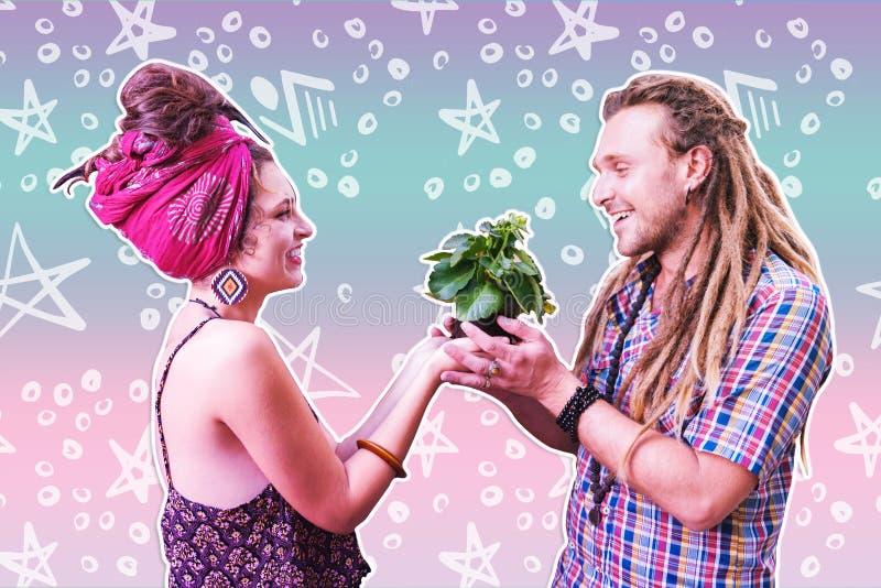 Coppie sorridenti piacevoli felici che tengono una pianta fotografie stock