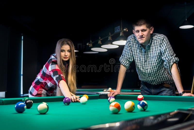 Coppie sorridenti in pub che gioca biliardo immagini stock