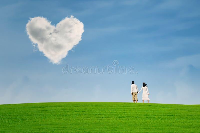 Coppie sotto la nuvola di forma del cuore fotografie stock libere da diritti