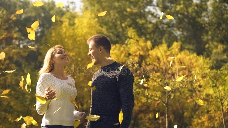 Coppie spensierate che godono delle foglie gialle che cadono, momenti puerili felici fotografie stock libere da diritti