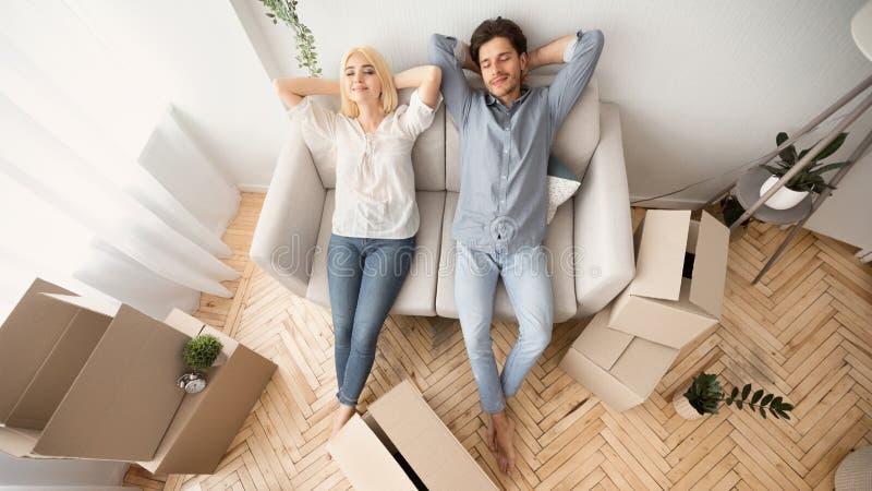 Coppie spensierate che riposano sullo strato in nuova casa, vista superiore fotografie stock