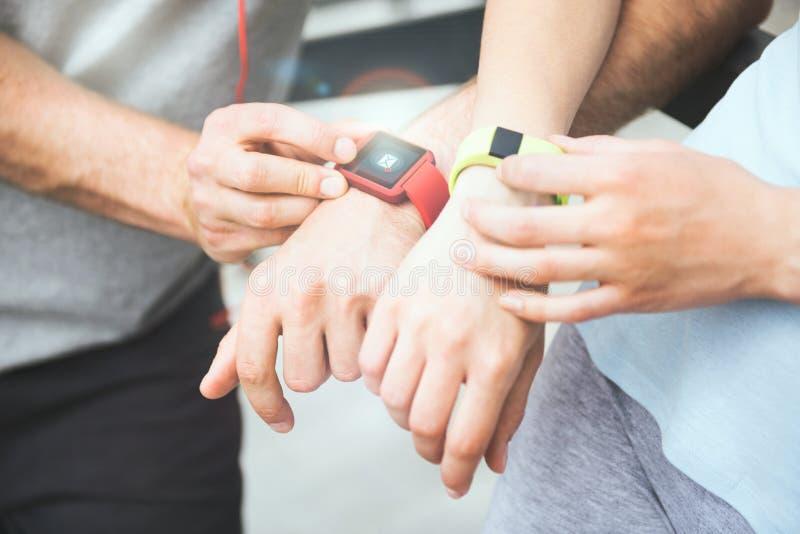 Coppie sportive che dividono i dati di allenamento dai loro smartwatches fotografia stock
