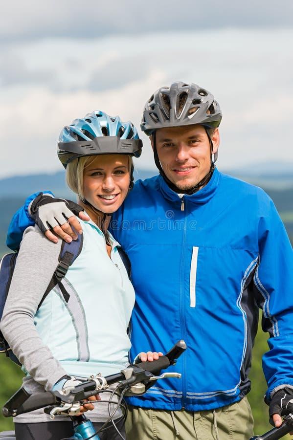 Giovani coppie sportive con i mountain bike in casco immagini stock libere da diritti