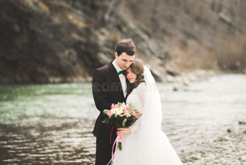 Coppie, sposa felice e sposo di nozze posanti fiume ordinato contro il contesto delle montagne immagini stock
