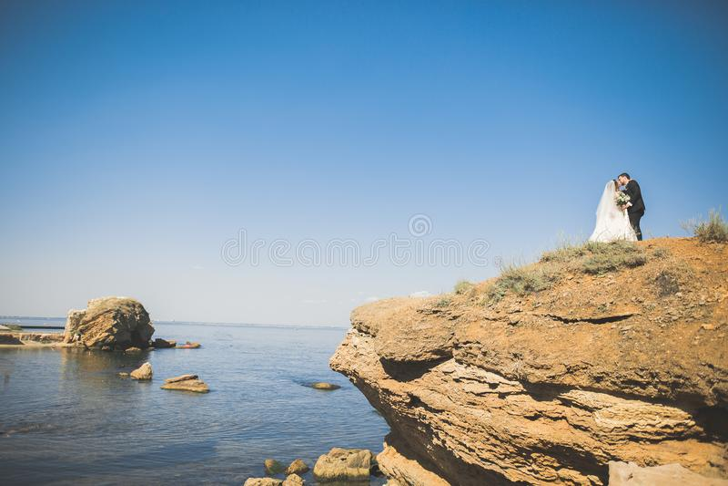 Coppie, sposo, sposa con il mazzo che posa vicino al mare e cielo blu di nozze immagine stock libera da diritti