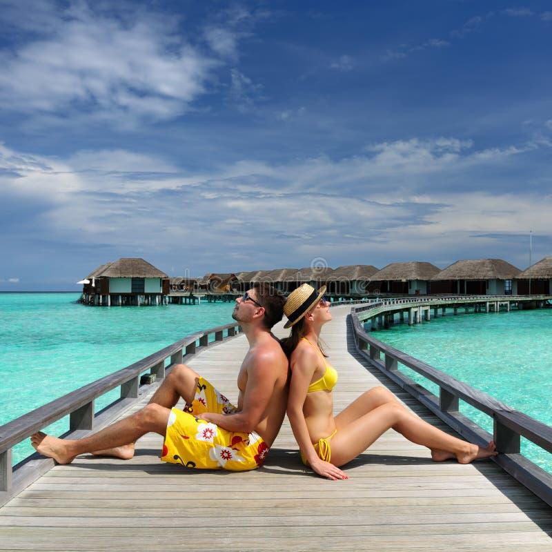 Coppie su un molo della spiaggia alle maldive fotografia for Disegni di casa sulla spiaggia tropicale