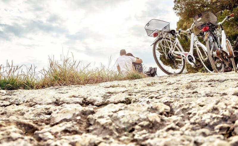 Coppie su un viaggio della bici Amanti che si siedono sulla spiaggia fotografie stock libere da diritti