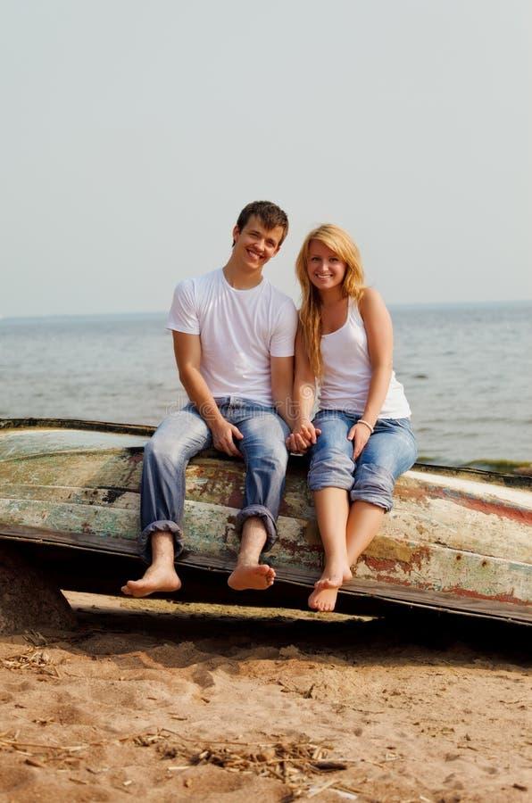 Coppie su una spiaggia che si siede sulla vecchia barca immagini stock