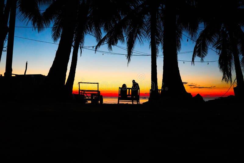 Coppie sul banco nella bella alba sul paesaggio tropicale del rong del KOH della spiaggia con le barche del longtail mentre il so immagine stock libera da diritti