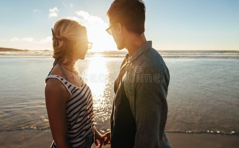 Coppie sulla spiaggia che esamina il tramonto immagine stock libera da diritti