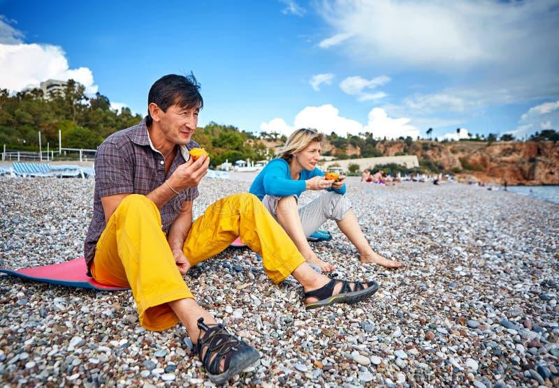 Coppie sulla spiaggia che mangia i cachi immagine stock libera da diritti