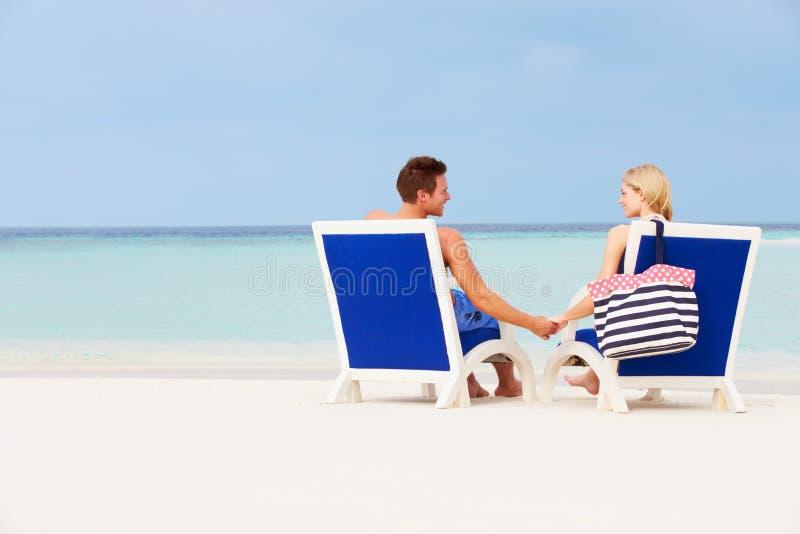 Coppie sulla spiaggia che si rilassa nelle sedie immagine stock