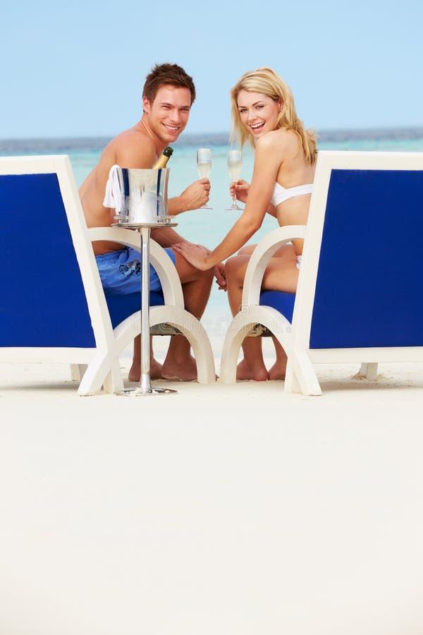 Coppie sulla spiaggia che si rilassa nelle sedie ed in Champagne bevente fotografie stock libere da diritti