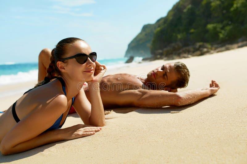 Coppie sulla spiaggia di estate Gente romantica sulla sabbia alla località di soggiorno immagini stock libere da diritti