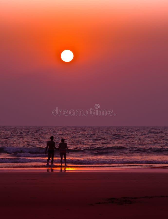 Coppie sulla spiaggia nel lignt di tramonto fotografia stock libera da diritti