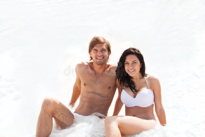 Coppie sulla spiaggia, sedentesi nel mare della schiuma dell'onda di acqua fotografia stock