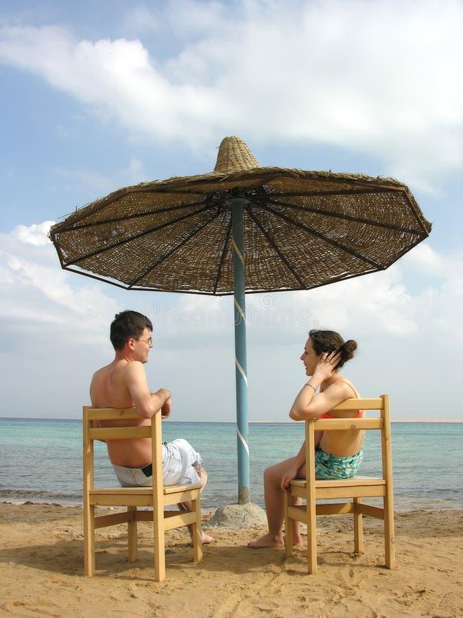 Coppie sulla spiaggia sotto l'ombrello fotografia stock libera da diritti