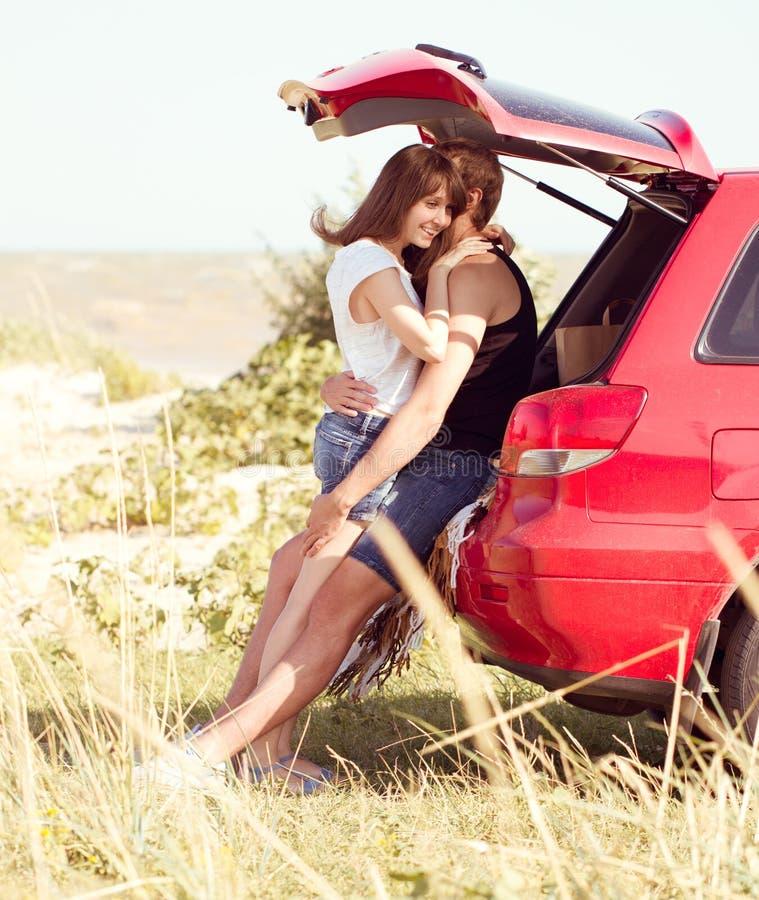 Coppie sulla spiaggia su un'automobile rossa immagine stock