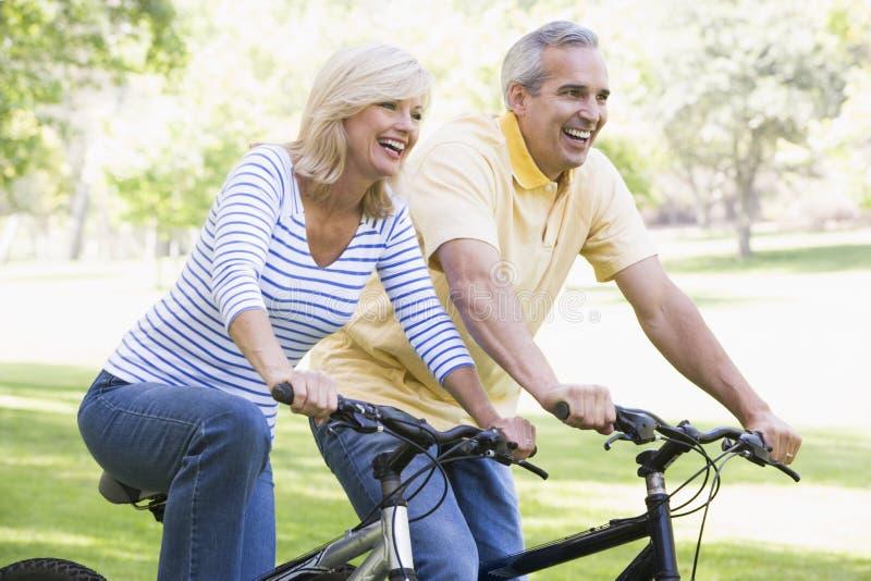 Coppie sulle bici all'aperto che sorridono fotografia stock