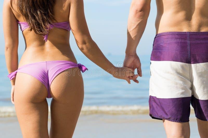 Coppie sulle vacanze estive della spiaggia, giovani nell'amore che camminano, tenersi per mano della donna dell'uomo immagine stock
