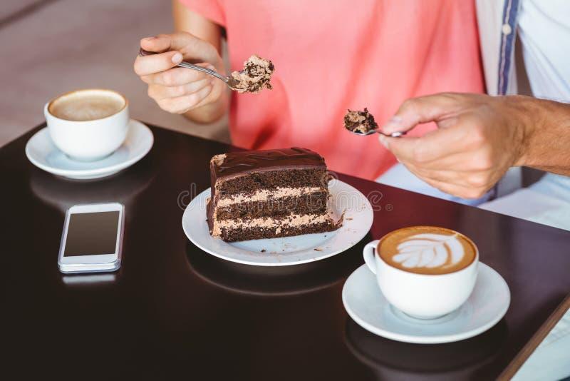 Coppie sveglie ad una data che divide un pezzo di dolce di cioccolato fotografia stock