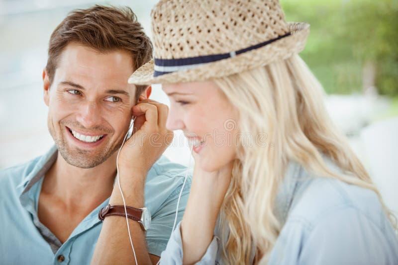 Coppie sveglie che ascoltano insieme la musica in caffè immagine stock