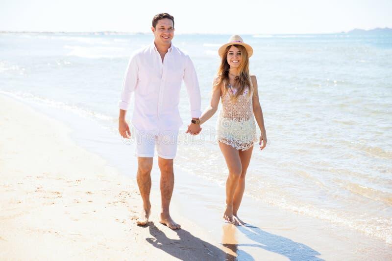 Coppie sveglie che camminano giù la spiaggia fotografie stock