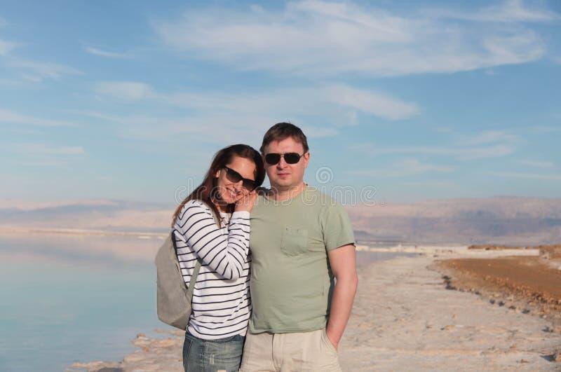 Coppie sveglie che godono del giorno luminoso sulla bella riva del sale del mar Morto l'israele fotografia stock libera da diritti