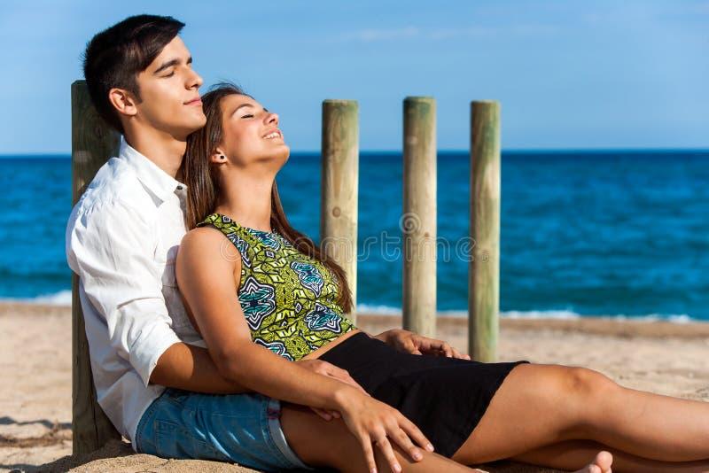 Coppie sveglie che si rilassano sulla spiaggia immagine stock libera da diritti