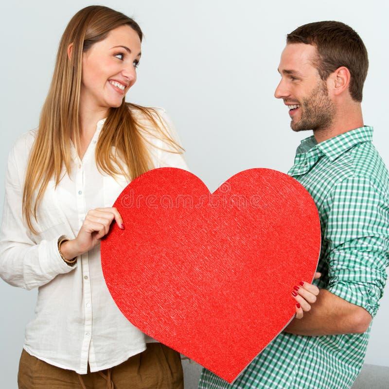 Coppie sveglie che tengono il grande segno rosso del cuore. immagini stock