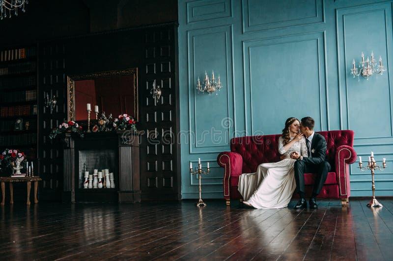 Coppie sveglie di nozze all'interno di uno studio classico che posa al sofà hey bacio ed abbracciarsi, tenendosi per mano esame immagini stock