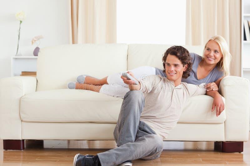 Coppie sveglie di risata che guardano TV immagine stock libera da diritti