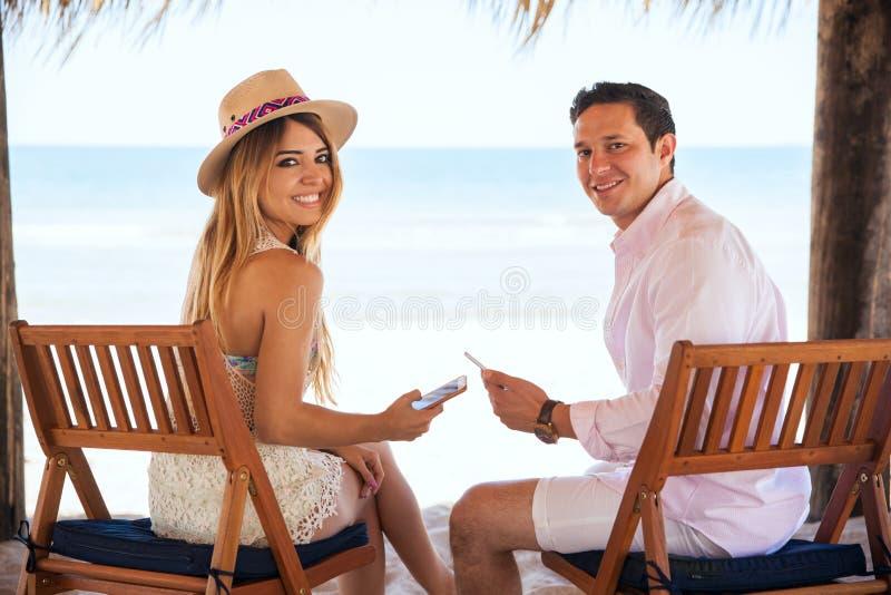 Coppie sveglie facendo uso dei loro smartphones alla spiaggia fotografia stock