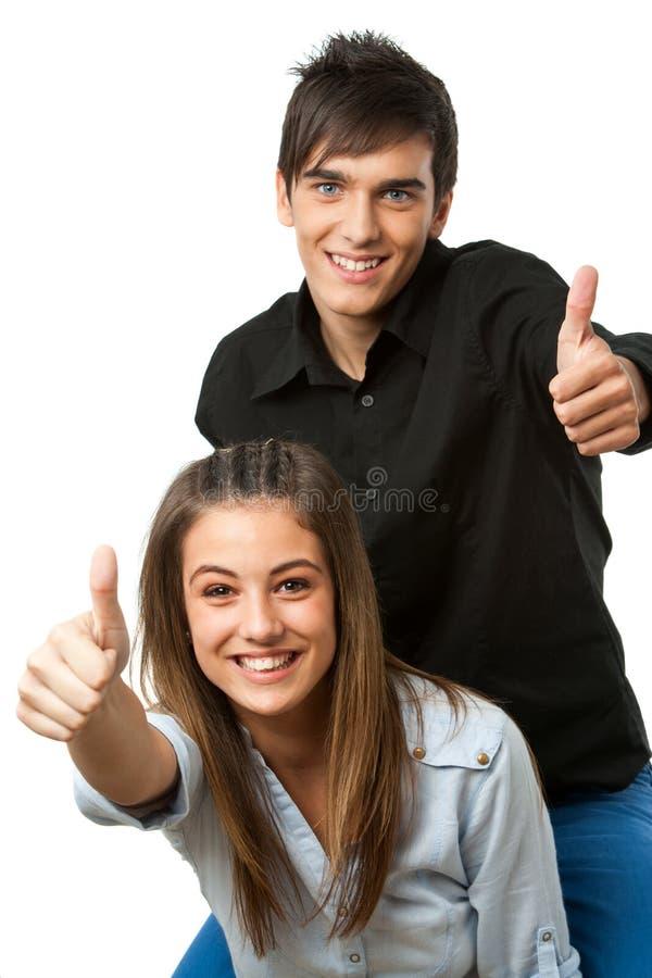Coppie teenager sveglie che mostrano i pollici in su. fotografia stock