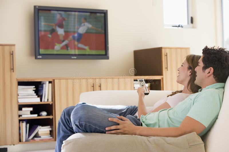 Coppie in televisione di sorveglianza del salone fotografia stock libera da diritti