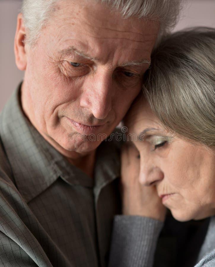 Coppie tristi dell'anziano su fondo marrone fotografia stock libera da diritti
